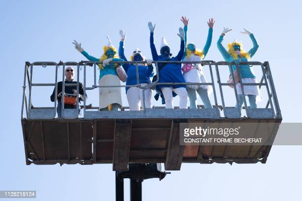 Participants wave from a lift before a gathering of people dressed as smurfs to be counted as part of a world record attempt on February 16 2019 in...