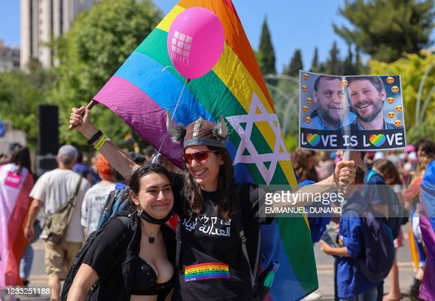 Participants wave LGBTQ rainbow flags during the annual Pride parade, as Israel lifted COVID-19 restrictions, in Jerusalem on June 3, 2021. -...