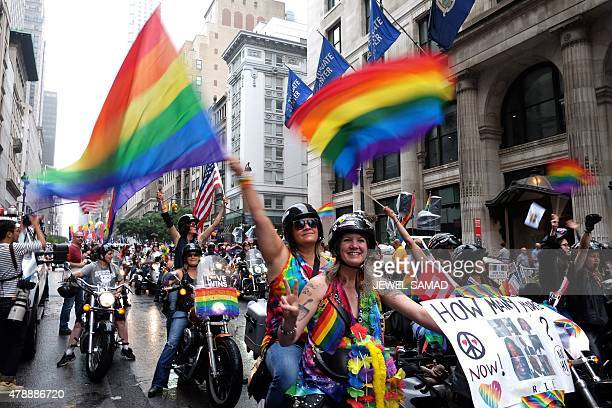 Participants wave rainbow flags while riding motorbikes during the 2015 New York City Pride march on June 28 2015 in New York Under a sea of rainbow...