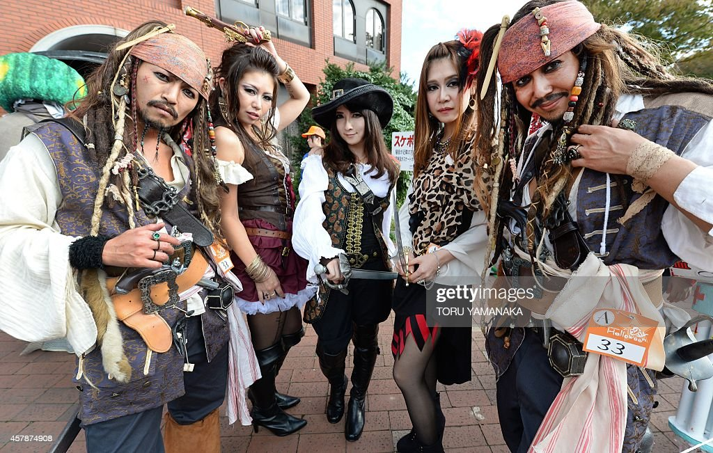 Participants wear costumes as they pose for pictures before the Halloween Parade in Kawasaki, a suburb of Tokyo, on October 26, 2014. More than 100,000 visitors watched the street costume parade in which some 2,500 people took part. AFP PHOTO/Toru YAMANAKA