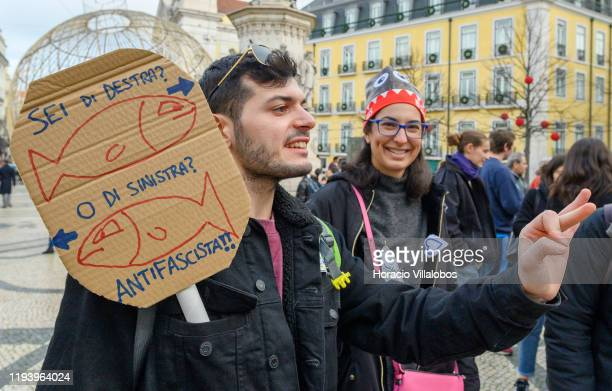 """Participants wear sardine hats and an anti fascist sign during a flash mob organized by Italian residents in Portugal as part of a global """"Sardina""""..."""