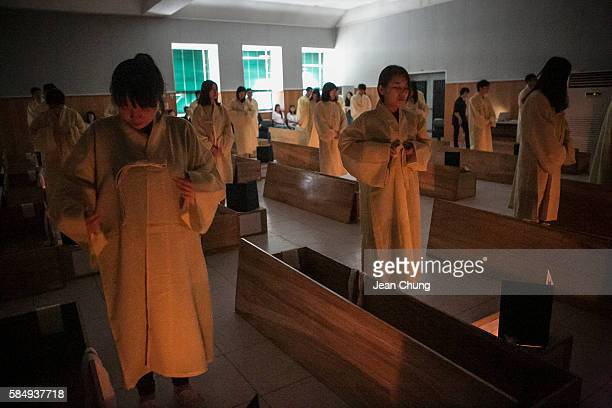 Participants wear the linen shrouds before lying down in a coffin during a Death Experience/Fake Funeral session held by Happy Dying on August 1 2016...