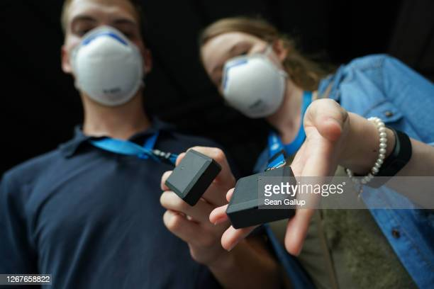 Participants wearing FFP2 protective face masks hold up their tracer devices at the RESTART-19 Covid transmission risk assessment study in a concert...