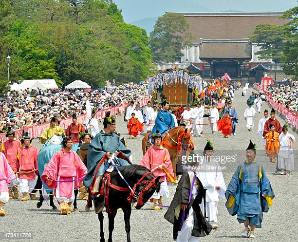 Participants wearing Heian Period dress decorated with heartshaped 'futabaaoi' leaves march on during the Aoi Festival on May 15 2015 in Kyoto Japan...
