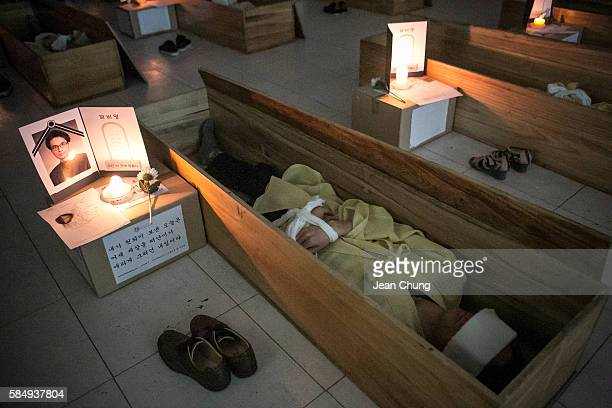Participants wearing linen shrouds meditate and reflect on their lives as they lie down in a coffin during a Death Experience/Fake Funeral session...