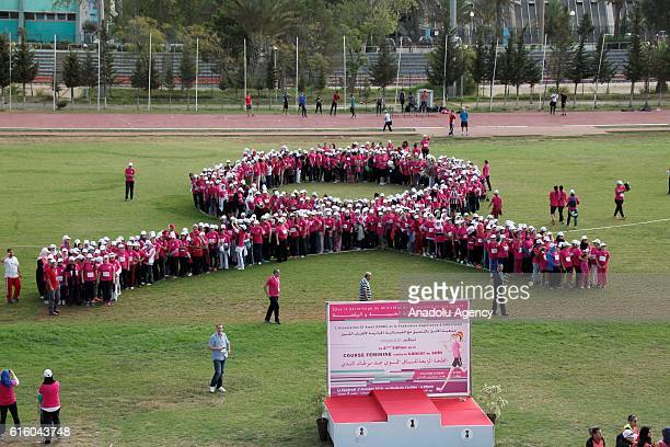 Participants wearing pink shirts form a human ''pink ribbon'' the symbol of breast cancer awareness during a Breast Cancer Marathon in Algiers...
