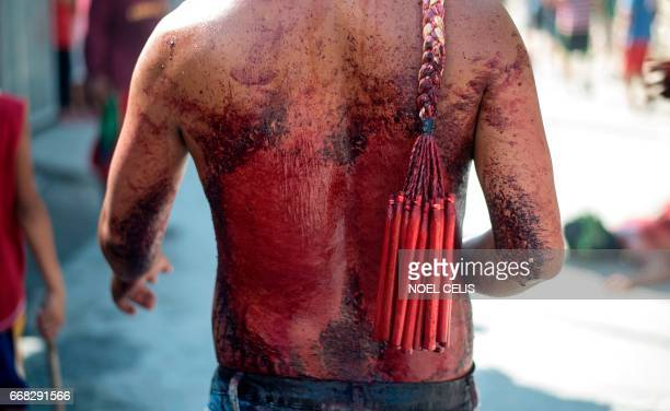 Participants whip their bloodied backs with bamboo as part of their penitence during the reenactment of the crucifixion of Jesus Christ for Good...