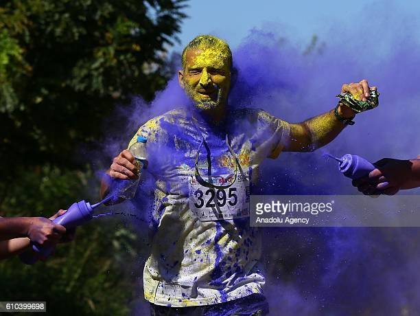 Participants with their faces and bodies painted with colours enjoy the 'Color Sky 5k' running fest at Inciralti in Izmir Turkey on September 25 2016