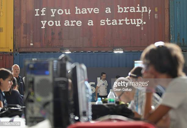 Participants work at computers under a logo written on a staqcked container that reads 'If you have a brain you are a startup' at the Campus Party...