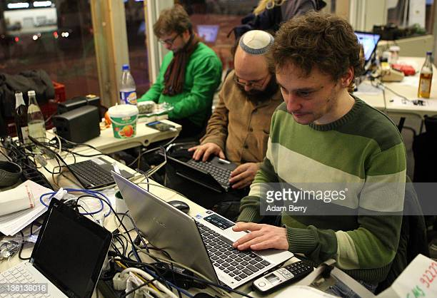 Participants work on laptops on the first day of the 28th Chaos Communication Congress Behind Enemy Lines computer hacker conference on December 27...