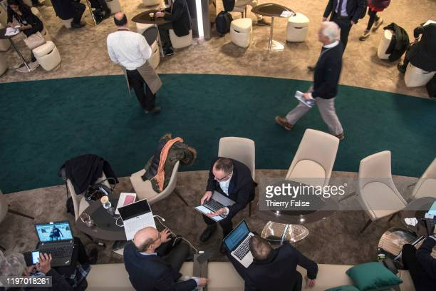 Participants work on their computers in a public lounge at the 50th World Economic Forum in Davos