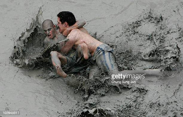 Participants wrestle in the mud during the 13th Annual Boryeong Mud Festival at Daecheon Beach on July 17 2010 in Boryeong South Korea Now in its...