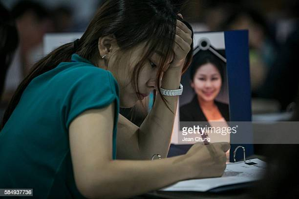 Participants write their biography and the words on their own tombstone while looking at their own funeral photos in a Death Experience/Fake Funeral...
