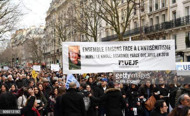 Participantswalk behind banners holding placards during a slient march in Paris on March 28 in memory of Mireille Knoll an 85yearold Jewish woman...