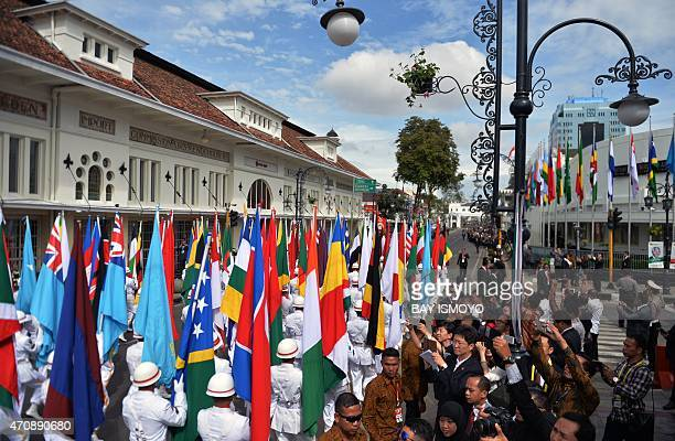 Participating countries' flags are paraded down the street ahead of a historical walk by heads of state during ceremonies marking the 60th...