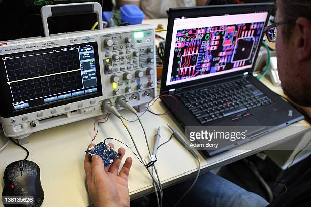 A particpant checks a circuit board next to an oscilloscope on the first day of the 28th Chaos Communication Congress Behind Enemy Lines computer...