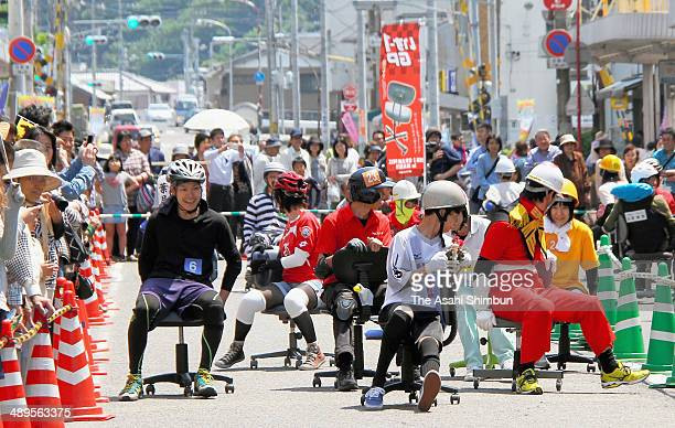 Particpants compete during the Office Chair Race on May 10 2014 in Naruto Tokushima Japan 28 3person teams compete by how much they can lap 150meter...