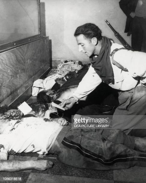 A partisan checking the cards on Benito Mussolini and Claretta Petacci's bodies Milan morgue April 30 Italy World War II 20th century