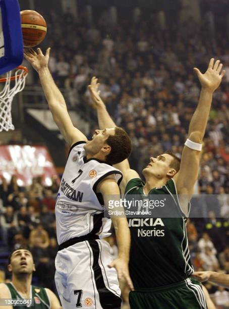 Partizan Belgrade player Dusan Kecman, left, scores over Panathinaikos Athens player Javtokas Roberts, right, from Lithuania, during their group B...