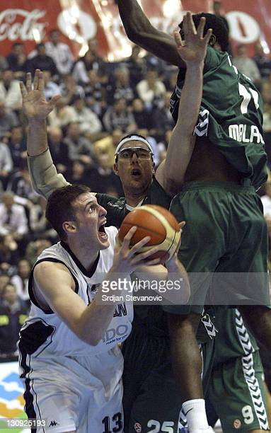 Partizan Belgrade player Kosta Perovic left is challanged by Daniel Santiago right from Unicaja Malaga during a group B Euroleague basketball match...