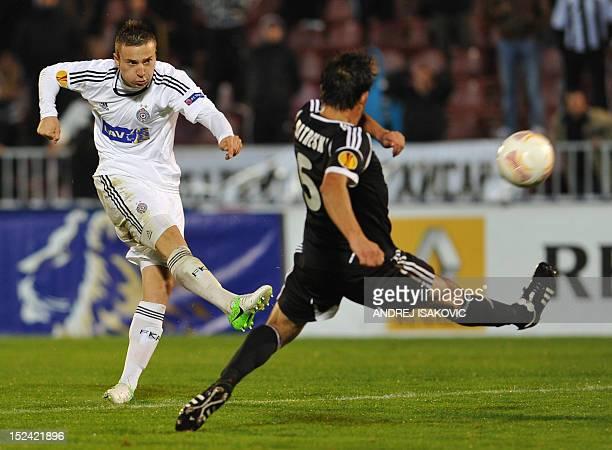 Partizan's Aleksandar Miljkovic shoots the ball in front of Neftchi's Igor Mitreski during the UEFA Europa League group H football match between...