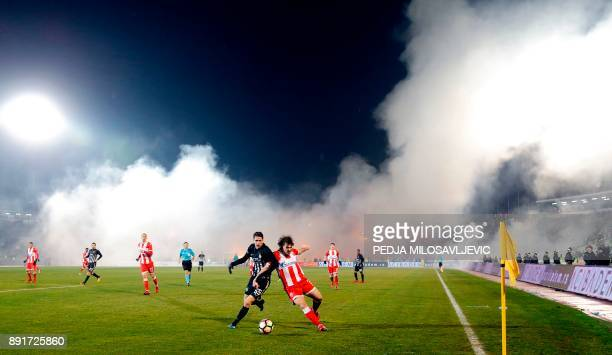 Partizan's Marko Jevtovic vies with Crvena Zvezda's Filip Stojkovic as smoke rise from the stands during the Serbian Superleague derby football match...