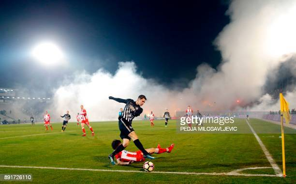 TOPSHOT Partizan's Marko Jevtovic vies with Crvena Zvezda's Filip Stojkovic as smoke rise from the stands during the Serbian Superleague derby...