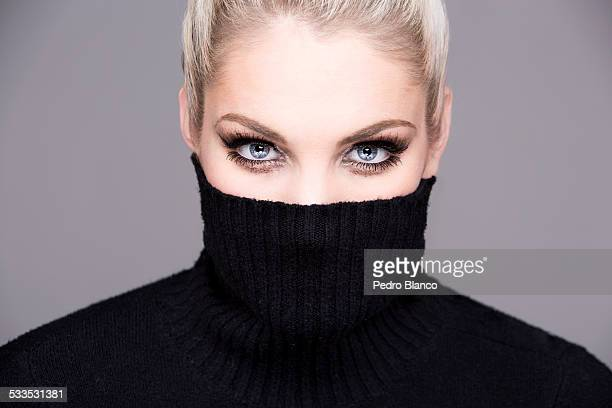 Partly covered head shot with black turtle neck.