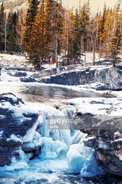 partly frozen elbow falls near bragg creek,alberta,canada - kananaskis country stock pictures, royalty-free photos & images