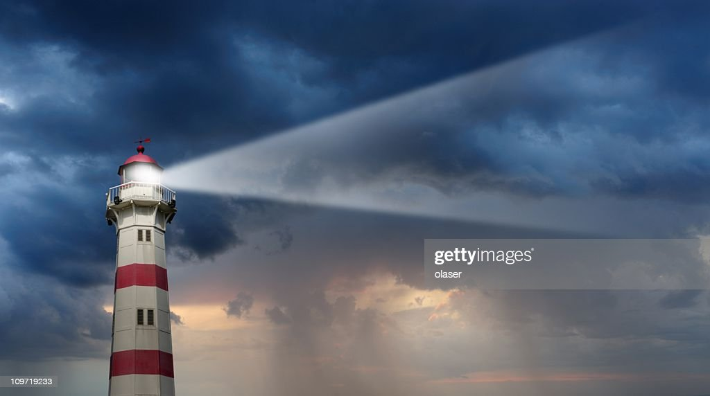 Partly sunlit lighthouse, bad weather in background : Stock Photo