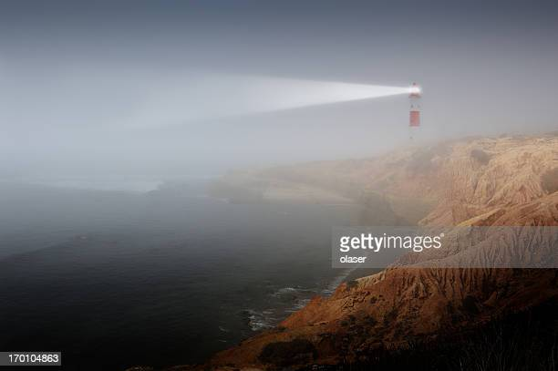 Partly sunlit rock with lighthouse
