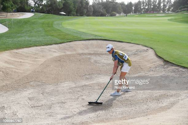 Partner and caddie for Lee Westwood of England, Helen Storey rakes a bunker on the 13th hole during Day Three of the Abu Dhabi HSBC Golf Championship...