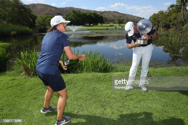 Partner and caddie Helen Storey sprays Lee Westwood of England with champagne after he wins during Day Four of the Nedbank Golf Challenge at Gary...