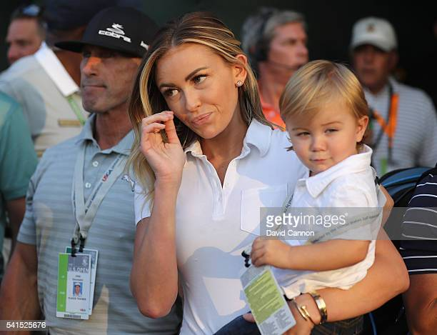 Partner Paulina Gretzky and son Tatum watch as Dustin Johnson of the United States finishes on the 18th green to win the US Open at Oakmont Country...