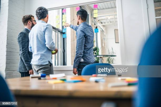 partners debating business ideas with post-it notes on the window - storyboard stock pictures, royalty-free photos & images