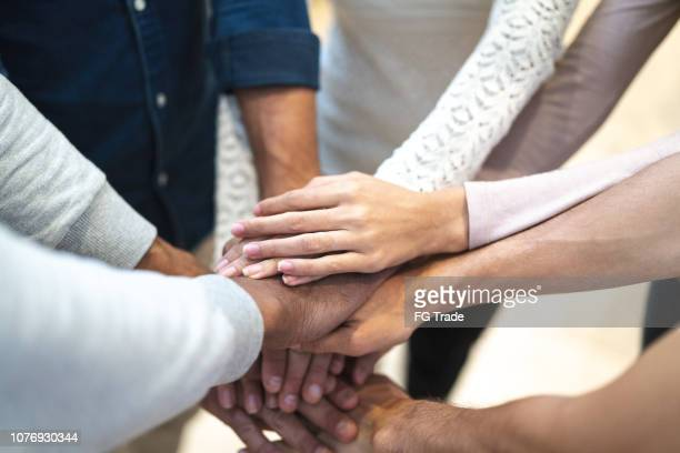 partners putting their hands on top of each other at workplace - hands clasped stock pictures, royalty-free photos & images