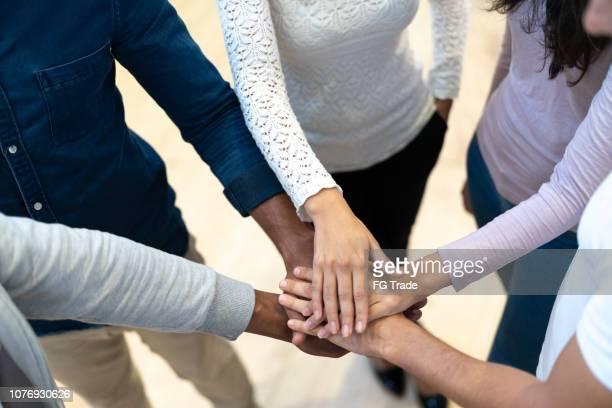 partners brengen hun handen op elkaar op werkplek - handen ineengevouwen stockfoto's en -beelden