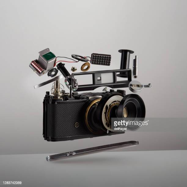 parts and components of a disassembled analog vintage film camera floating in the air on white background - dismantling stock pictures, royalty-free photos & images
