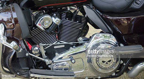 Parts of a Harley Davidson motorcycle are seen in closeup view The shiny polished chrome and steel parts reflect the images of nearby objects and a...