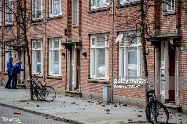 Parts of a roof lie on the pavement in front of a porch house in Rotterdam The Netherlands on January 18 during the second winter storm of the month...