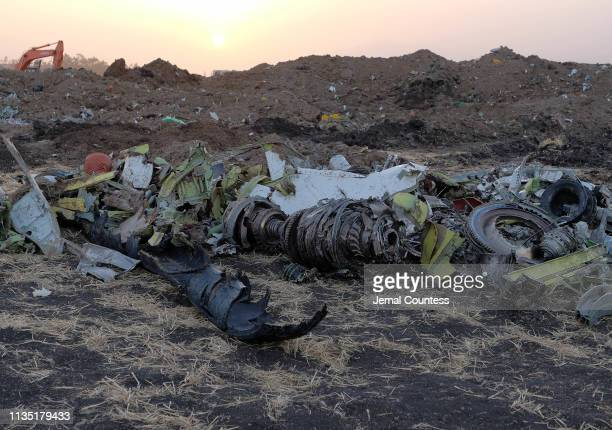 Parts of an engine and the landing gear lie in a pile after being gathered by workers during the continuing recovery efforts at the crash site of...