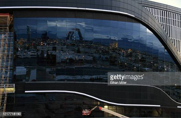 Parts of the city are reflected off the side of Allegiant Stadium the USD 2 billion glassdomed future home of the Las Vegas Raiders under...