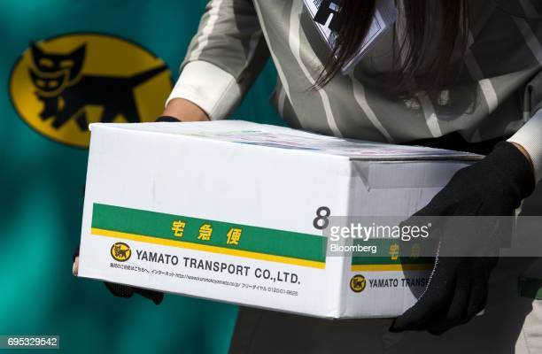A parttime employee of Yamato Transport Co called 'field cast' by the company carries a parcel for distribution outside a residential building in...
