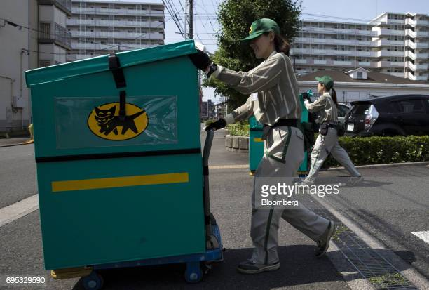 Parttime employees of Yamato Transport Co called 'field cast' by the company push carts loaded with parcels for distribution near residential...