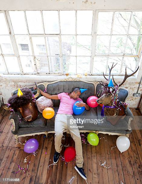 party animals passed out on couch after a big night - house after party stock pictures, royalty-free photos & images