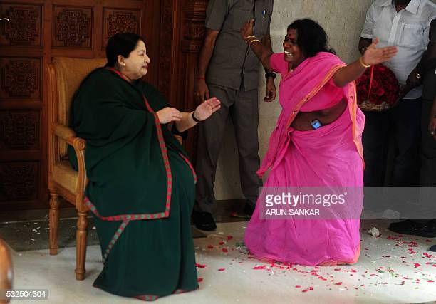 A party cadre celebrates victory with All India Anna Dravida Munnetra Kazhagam leader Jayalalithaa Jayaram as she gestures at her residence in...