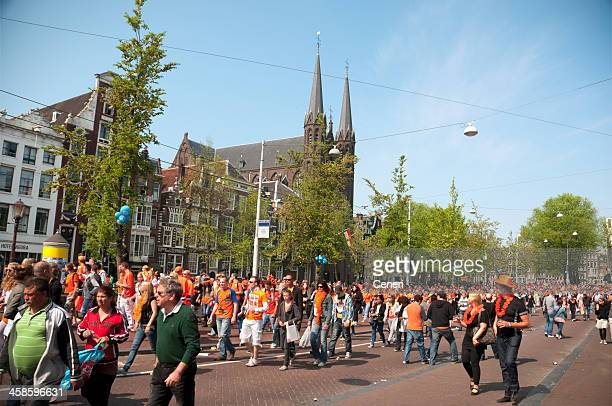party crowd on queen's day in amsterdam, netherlands - king's day netherlands stock photos and pictures