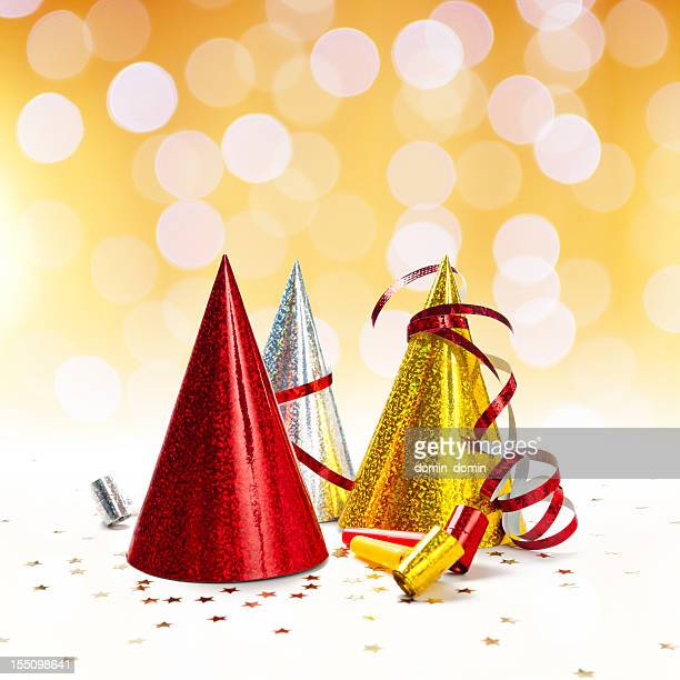 Party decorations: hats, whistles, streamers, confetti golden lights background