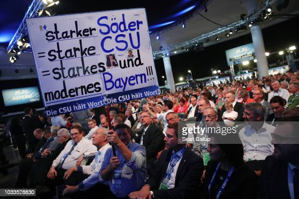 CSU party delegates and members including one holding a sign that reads Strong Soeder strong CSU strong and modern Bavaria attend the party congress...