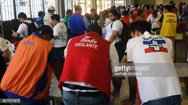 Party delegates are pictured at a polling station during legislative and municipal elections in San Salvador on March 4 2018 Legislative elections in...